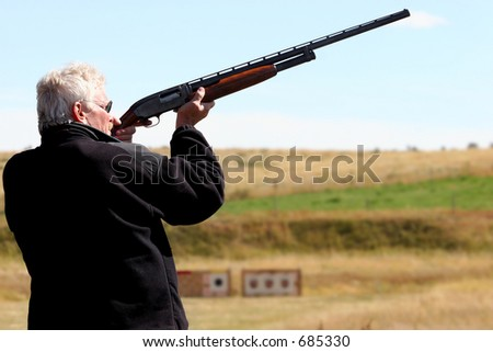 Man firing shotgun at sporting clays in preparation for hunting season. - stock photo