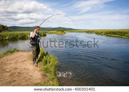 Man fishes caught salmon from the river. Far East Russia. - stock photo