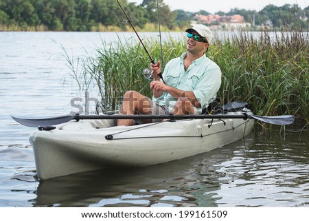 Man fishing from kayak on a beautiful day at dusk. - stock photo
