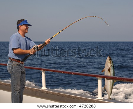Man fishing from the edge of a moving boat with a live yellow tail tuna hanging from the fishing line - stock photo