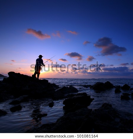 Man fishing in last rays of sunlight on sea shore,Thailand
