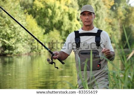 Man fishing in river - stock photo