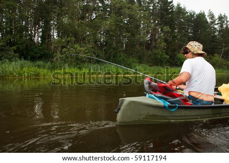Man fishing in river from canoe - stock photo