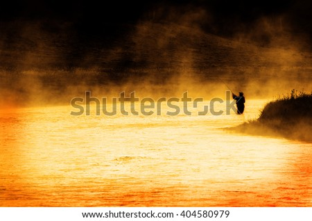 Man fishing in river or lake silhouette by sunrise and misty water - stock photo