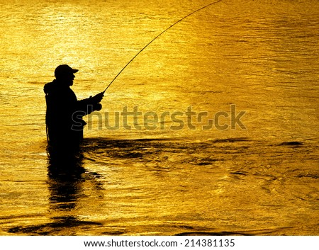 Man fishing in river with fly rod and waders - stock photo