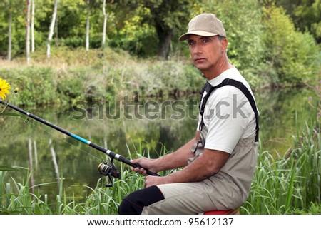 Man fishing in stream - stock photo