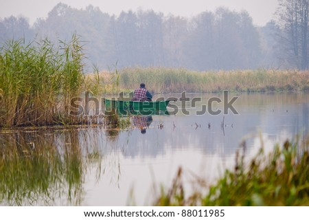 man fishing in the boat on the lake - stock photo