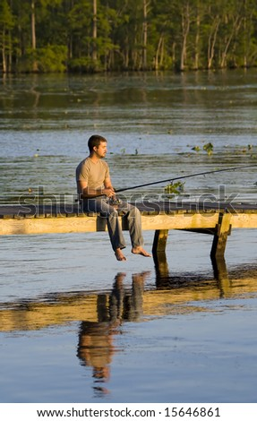 Man fishing off of a dock into a bay as the sun is setting.
