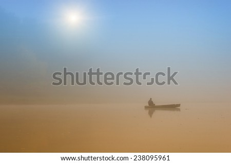 Man fishing on a boat on foggy morning - stock photo