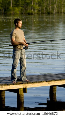 Man fishing on a dock in a bay as the sun in setting. - stock photo