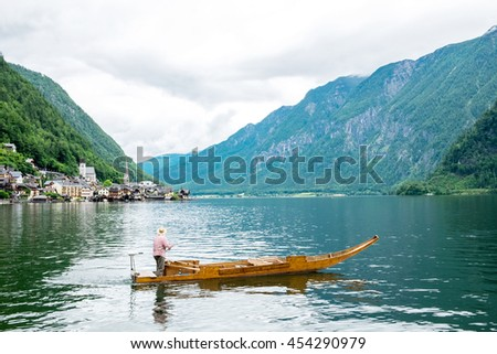 man fishing on a lake from the boat at Hallstatt