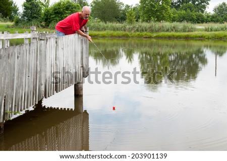 Man fishing on pier - stock photo