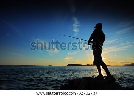 Man fishing on sunset - stock photo