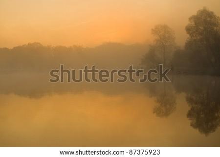 man fishing on the river at sunrise - stock photo
