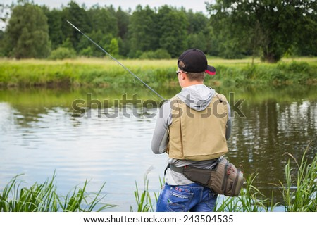 Man fishing on the river bank. Young spinningists fishing. Male professional fisherman caught fish. - stock photo
