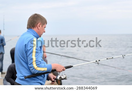 Man fishing with a rod and reel from a jetty with friends on a cold misty day, side view upper body - stock photo