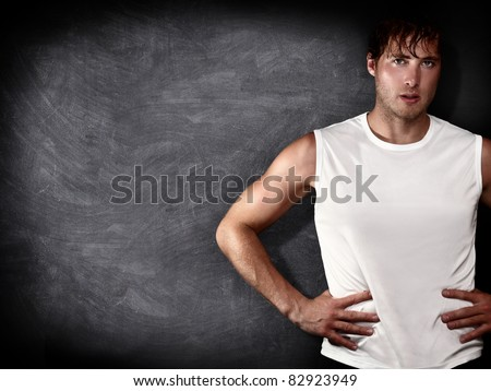 Man fitness model in front of empty blackboard / chalkboard with copy space for text, message or design. Caucasian male fit model on black background. - stock photo