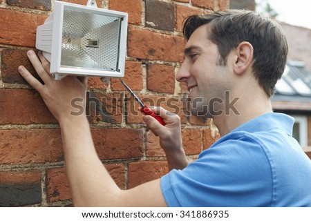 Man Fitting Security Light To House Wall - stock photo