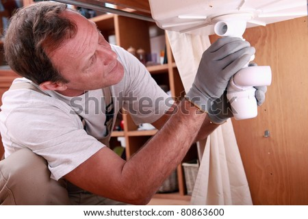 Man fitting the waste on a kitchen sink - stock photo