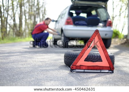 man fixing a car problem after vehicle breakdown on the road - stock photo