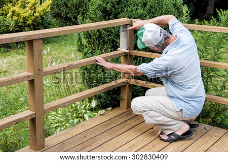 Man fixing a deck railing  - stock photo