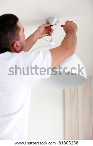 Man fixing ceiling light - stock photo