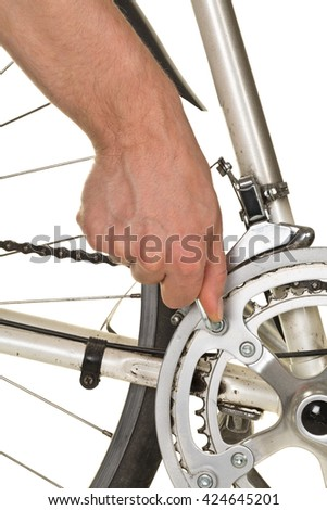 Man fixing chainring on a bicycle on white background  - bike repair concept - stock photo