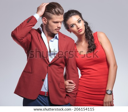 man fixing his hair and looks away, woman looks at the camera - stock photo