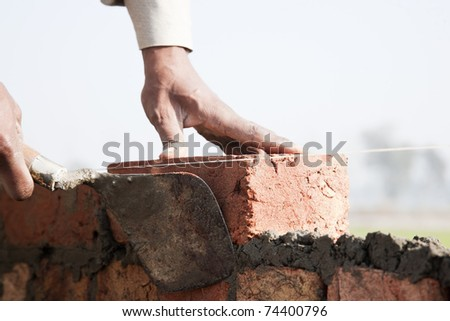 man fixing the brick of a wall. - stock photo