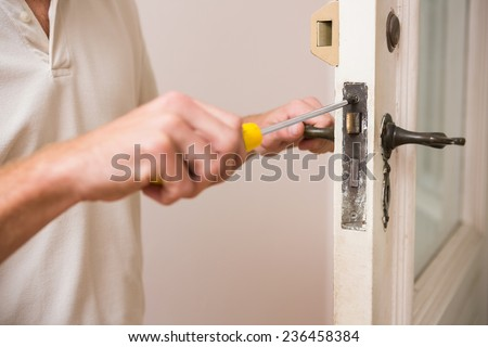 Man Fixing The Door Handle With Screwdriver In A New House
