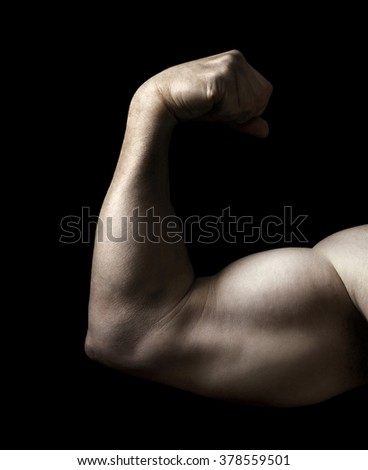 Man Flexing Bicep Muscle on a Black Background - stock photo