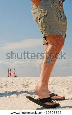 Man Flexing Tattoo with Ladies in Distance - stock photo