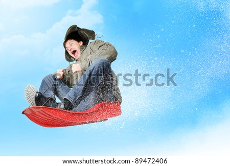 Man flies on sled in the snow - stock photo