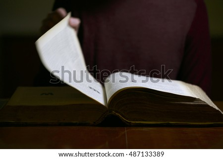 Man Flipping through the Pages of an old book