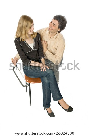 Man flirting with a woman sawing her chair leg - stock photo