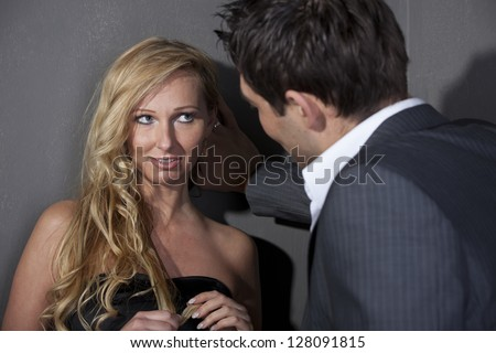 Man flirting with a woman standing at the wall - stock photo