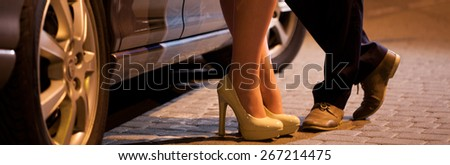 Man flirting with prostitute next to his car - stock photo