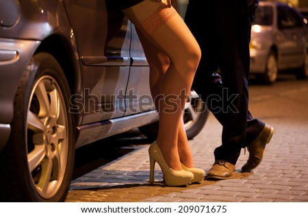 Man flirting with prostitute on the street - stock photo