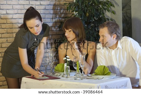 man flirting with waitress during a dinner with his girlfriend - stock photo