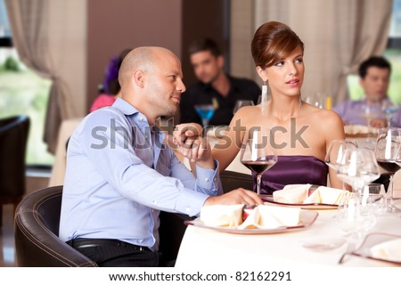 man flirting, woman distracted at restaurant table - stock photo