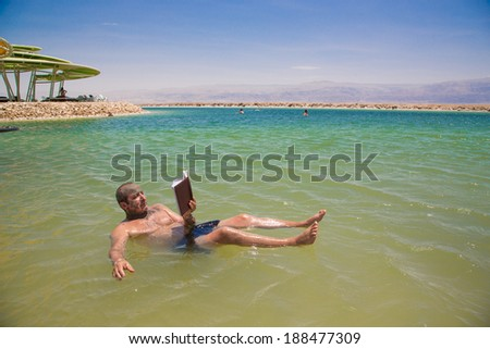 Man floating and reads a book at the Dead Sea - stock photo