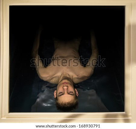 Man floating in a sensory deprivation isolation tank filled with dense salt water used in meditation, therapy, and alternative medicine. The boarders of the tank gives context. - stock photo