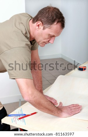 Man folding a drawing - stock photo
