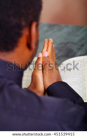 Man folding hands praying with open bible lying in front, seen from behind models head, religion concept - stock photo