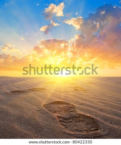 man footprint on a sand at the sunset
