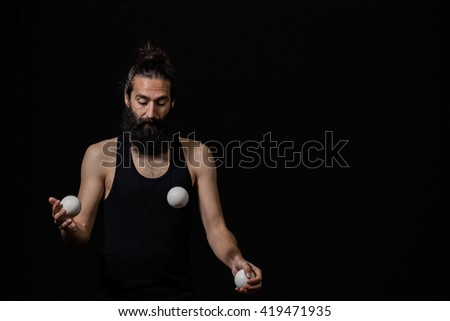 Man fully focused on his juggling performance at the circus. Mindfulness / concentration concept. - stock photo
