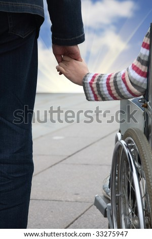 man gently holds by the hand the woman in an invalid carriage - stock photo