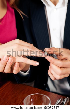 Man gently sticks a diamond ring on the finger of his fiance after a romantic dinner (just hands to be seen) - stock photo