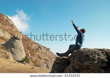 Man gesturing with raised arms with rocks landscape background - stock photo
