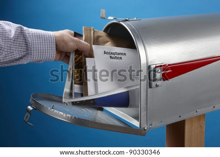 Man gets mail from an open mailbox - stock photo